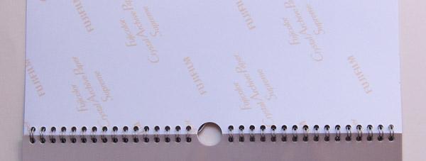 Der Kalender auf Fotopapier wird durch eine silberne Ringbindung gehalten.